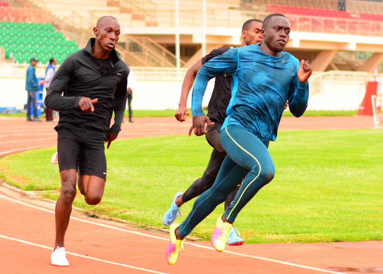 Mike Mokamba charges past Jared Momanyi and Elijah Matayo during a training session at Nyayo stadium.