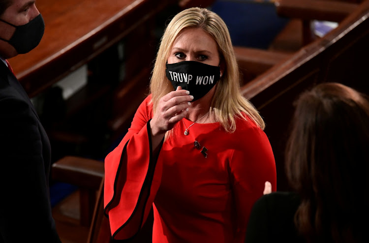 "U.S. Rep. Marjorie Taylor Greene (R-GA) wears a ""Trump Won"" face mask as she arrives on the floor of the House to take her oath of office."