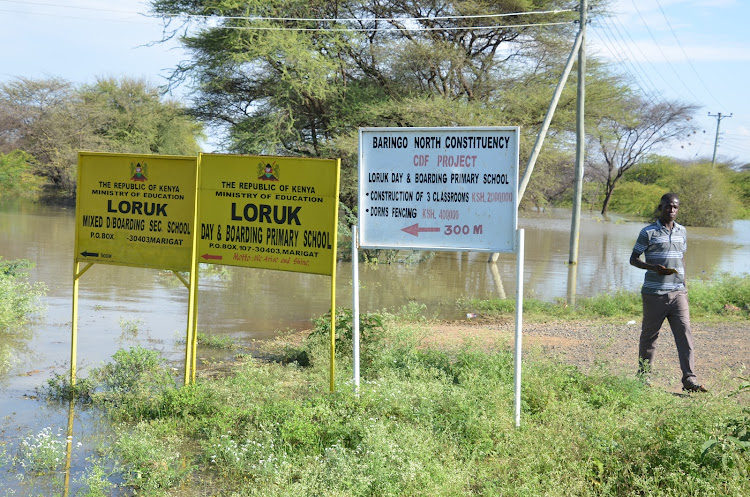 A man walks past flooded Loruk Primary School sign post in Baringo on Monday, October 12, 2020.