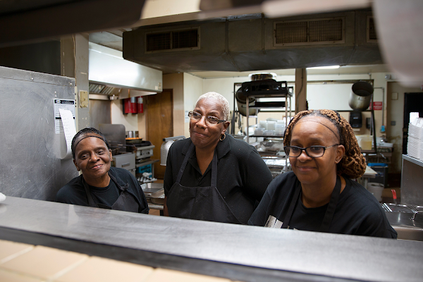 Three employees of the Four Way Restaurant stand behind a serving counter, ready to serve up smiles.