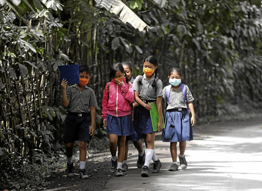 Children wear masks as they walk to school in an area affected by volcanic ash from nearby Mount Agung volcano, in Karangasem Regency, Bali, Indonesia. Picture: REUTERS