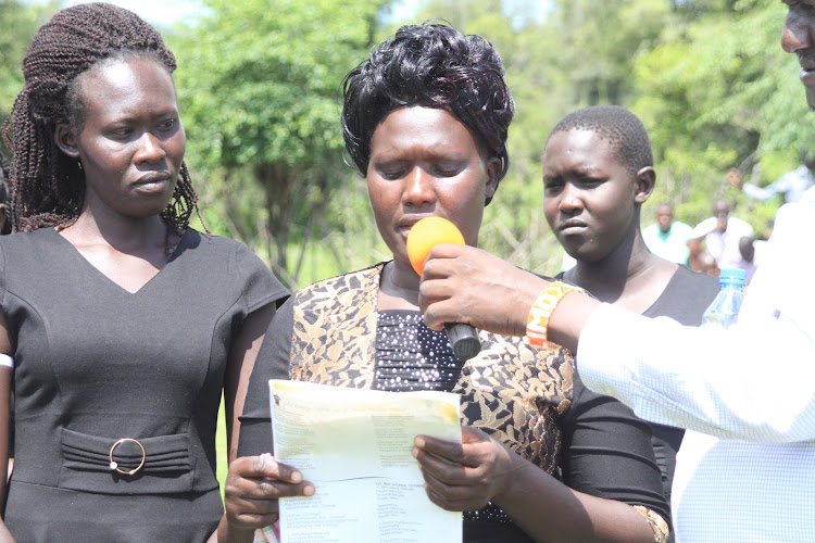 Josephine Kimoi(centre), widow of the elephant attack victim Jackson Chepyegon, 40, reads the eulogy during burial at his Sessunin home in Barwessa ward, Baringo North Sub-county on Saturday.