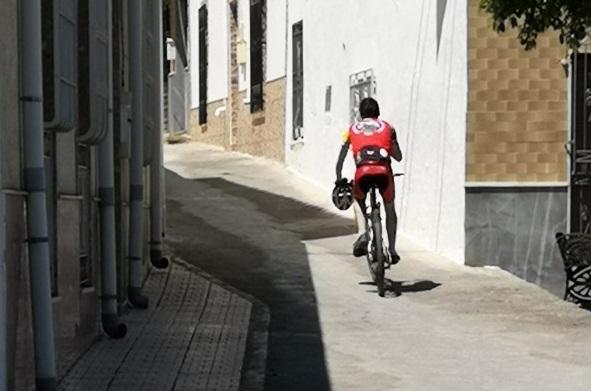 Un ciclista escala una empinada calle en Íllar.