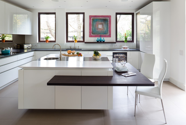 unique modern kitchen island with an attached dining table. white countertops and simple frameless white cabinetry
