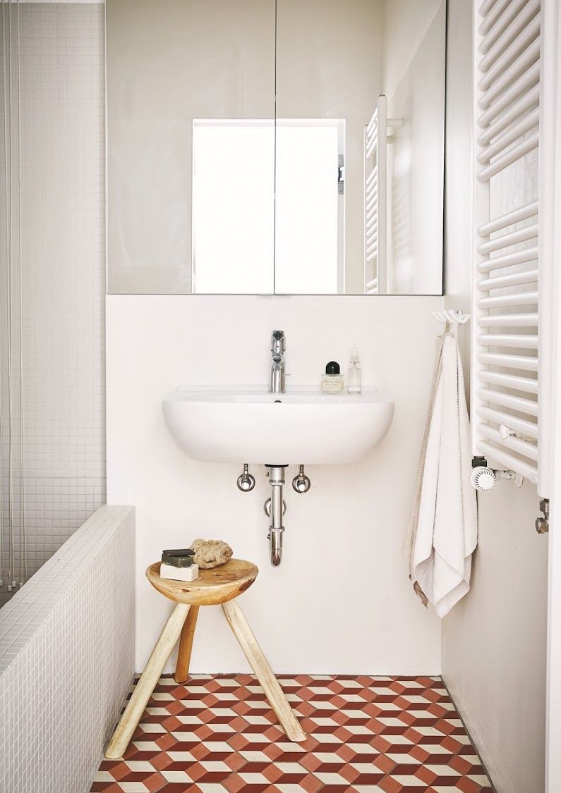 The bathroom is sleek and minimalist; it's tiled with patterned, untreated cement tiles.