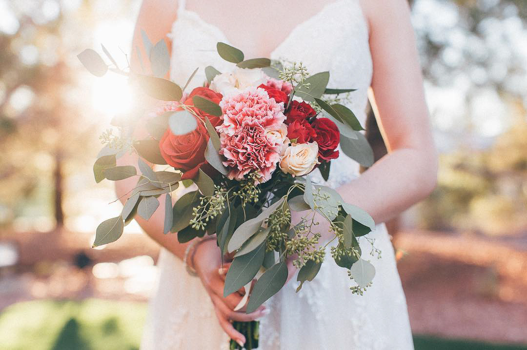 Mid closeup shot of a bride holding a bridal bouquet with bright-colored flowers in her hands