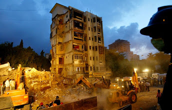 Photo: Firemen and volunteers look on as an excavator removes the debris of a collapsed building in Mumbai, India, Thursday, July 19, 2007. At least 22 people were killed and nine others wounded when a building collapsed in Mumbai late Wednesday, officials said Thursday. At least 10 others were feared trapped in the rubble of the residential building, said Gopal Shetty, a state lawmaker. (AP Photo/Gautam Singh)