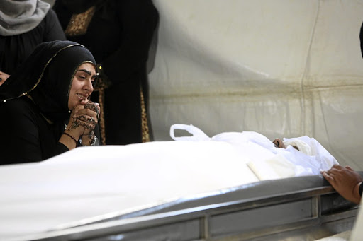 Sakina Essop, the widow of Abbas Essop, grieves at her husband's side before the burial.