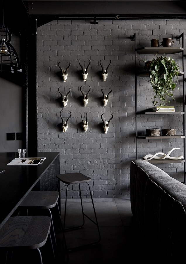 Against the grey facebrick, a collection of skulls creates an arresting wall feature in the open-plan living area.