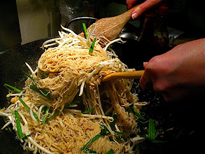 Photo: tossing rice stick noodles with spiced coconut sauce, bean sprouts and garlic chives