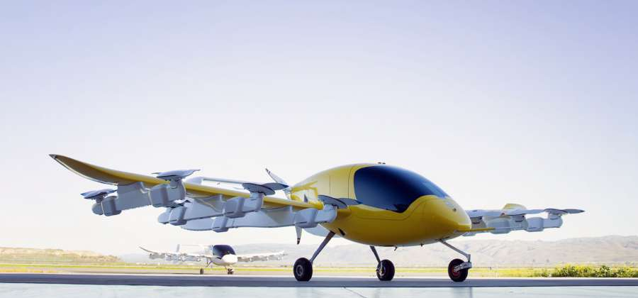 A yellow colored electric aircraft with an oval cockpit and 6 pairs of propellers on its wings