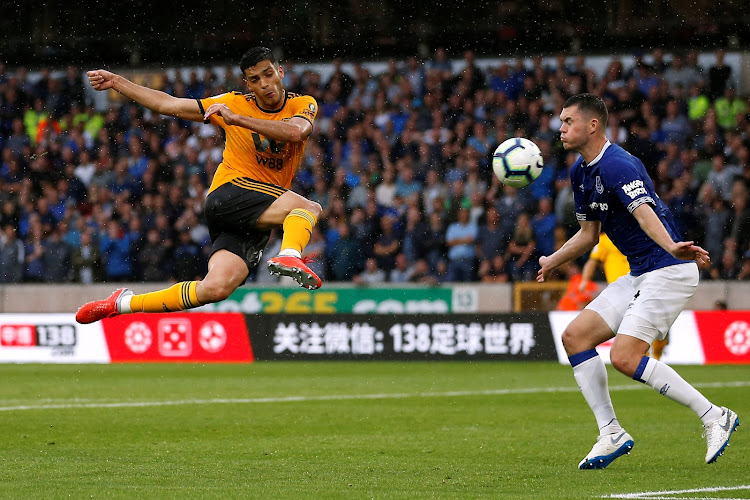 Wolverhampton Wanderers' Raul Jimenez shoots at goal under pressure from Everton's Michael Keane during a Premier League match at Molineux Stadium, Wolverhampton, on August 11, 2018.