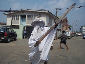 Photo: Eyo Akogu Olofin of Lagos on pose for a picture in Obalende area of Lagos as a pedestrain walks by, barefooted