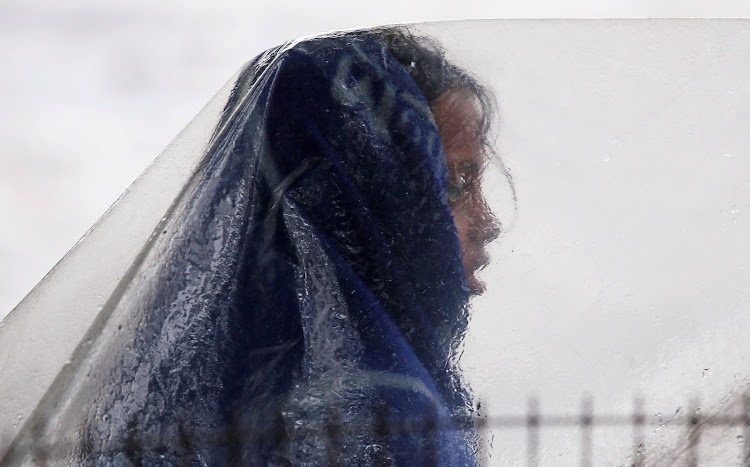 A girl sits under a plastic sheet as it rains in the old quarters of Delhi.