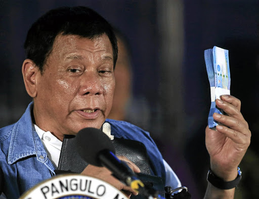 Philippines' President Rodrigo Duterte holds Philippine peso bills for the Marawi evacuees during his visit at the Iligan City National School of Fisheries evacuation centre in Iligan City, Philippines, on June 20, 2017. Picture: REUTERS/ROMEO RANOCO