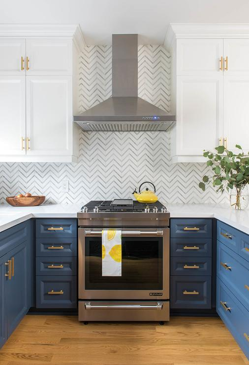 blue and white kitchen with brass cabinet hardware, white countertops, wood floors and stainless steel range hood