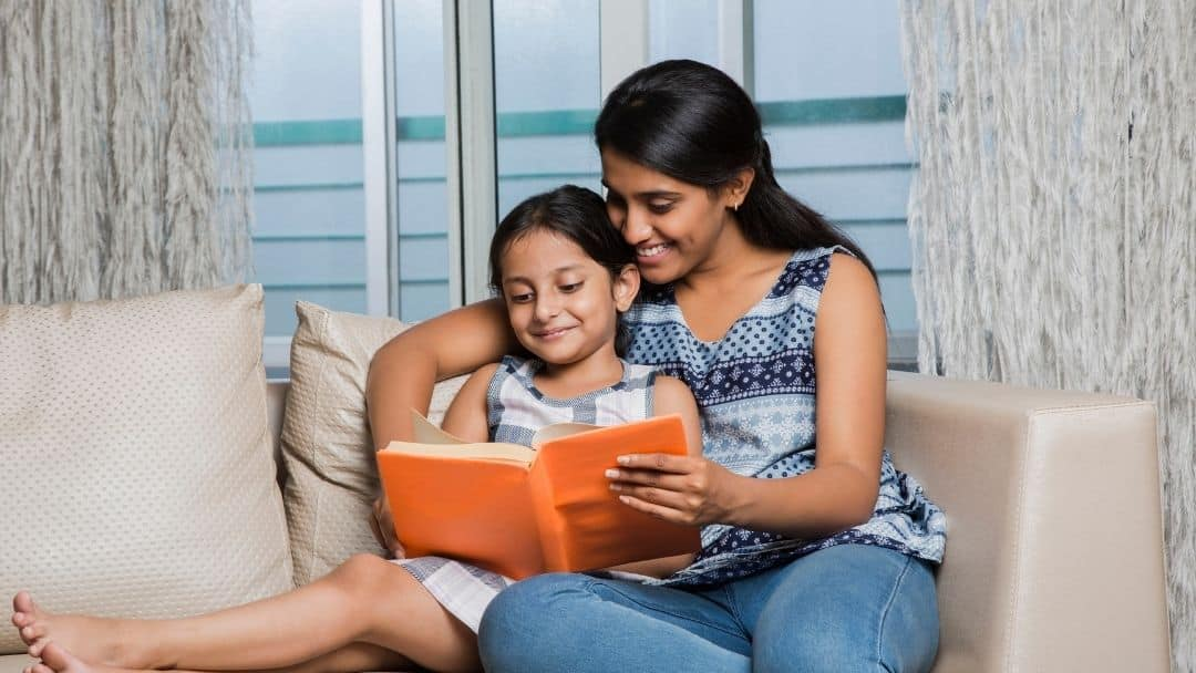 mother and daughter reading an orange book on the couch together