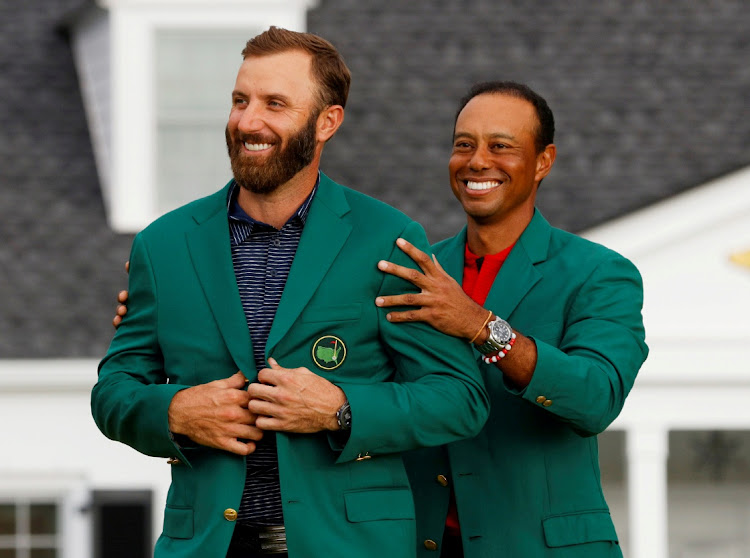 Defending champion Dustin Johnson is presented with the green jacket by Tiger Woods after winning the US Masters at Augusta National Golf Club on November 15 2020.