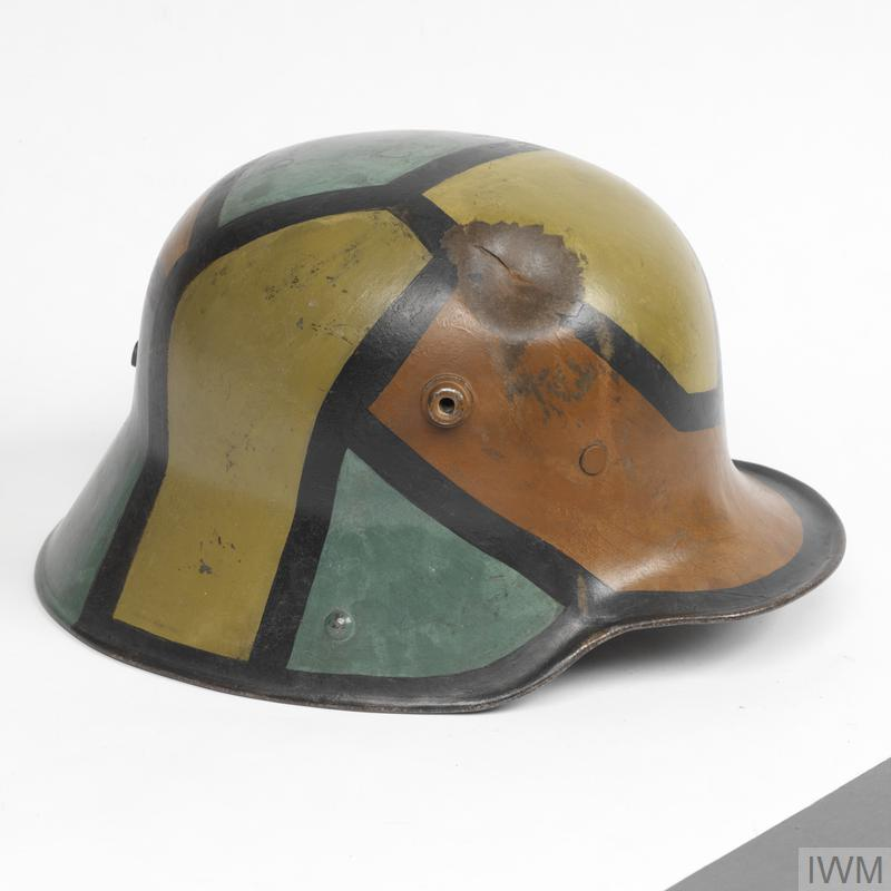Helmet: Model 1916 steel helmet, complete with leather three-pad liner attached to a leather headband. The inside is painted regulation dark apple green and externally is hand-painted in camouflage segments of red-brown, light-green and dark yellow, all outlined with a black border, 15mm in width. To the upper right front crown is an impact dent that has fractured the metal 40mm in length.
