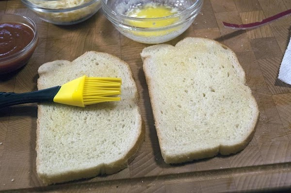 Take two of the bread slices, and brush one side with the melted butter.