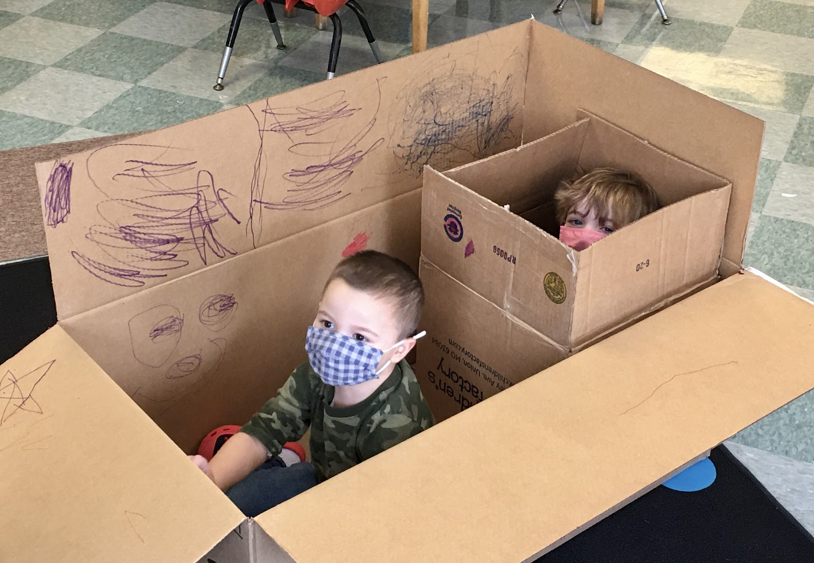 masked students sitting in cardboard boxes
