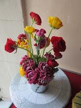 Photo: création piquée dans de la mousse synthétique  fleurs utilisées: oeillets violets, renoncules rouge et jaune,mousse des bois. contenant sceau en zinc .  prix 15 euros