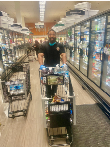 Man in grocery store pushing shopping cart and smiling