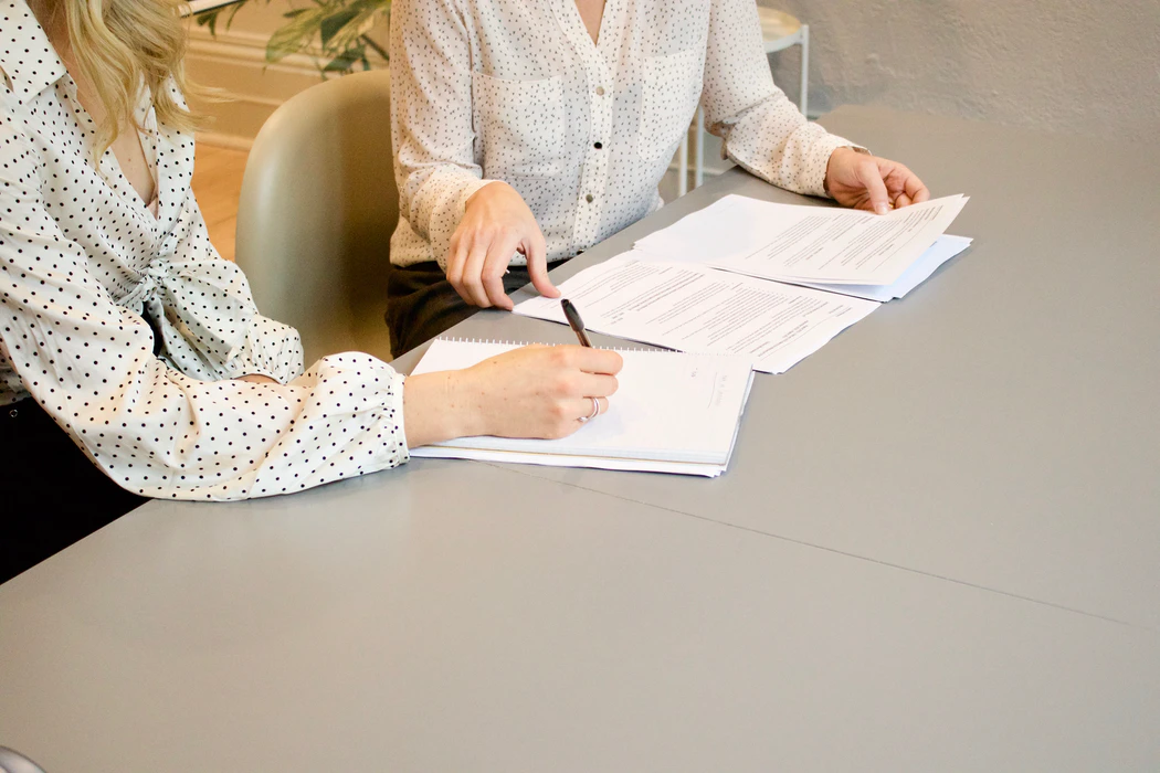 two women signing papers