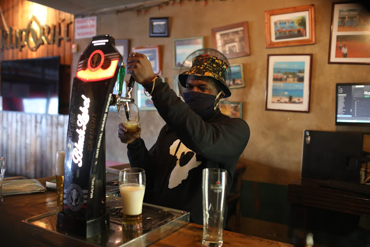 A bartender in Melville, Johannesburg, wears a mask while pouring beer during eased lockdown restrictions. Less than 2,000 new cases of Covid-19 were again reported across SA on Wednesday.