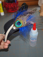 Photo: Add your decorations of choice.  (Use a pinchy style clothes pin to hold things in place as the glue dries.)  I added a plume of feathers and a tiny cameo button.  (The button had a shank which I cut off with wire cutters.)  I highly recommend Fabri-Tac  glue.  It grabs tight so trims don't slide around while your working and it dries fast and clear.