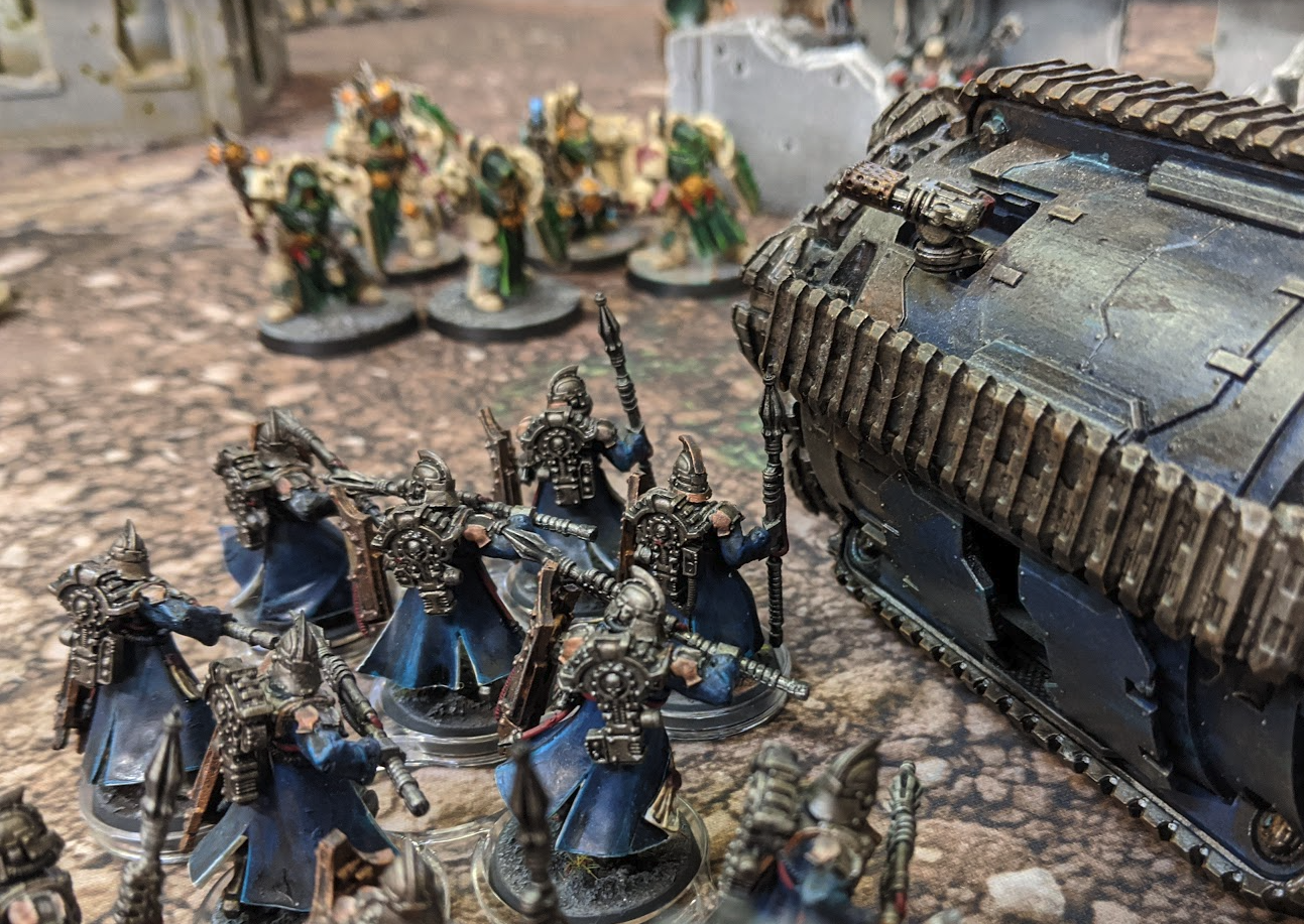 A warhammer game in progress with a close up of a drill-like vehicle and blue robed miniatures facing off space marines