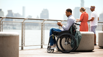Man in wheelchair using Android on a pier.
