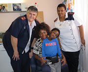 A happy, smiling Mnotho Mndebele safely in the arms of his mother, Mbali Mndebele, while showing off his heart ventricular assist device (HVAD). On hand to offer support is sister Ina Kok, acting deputy nursing manager (left) and Sr Bulelwa Ntilashe, a registered nurse.