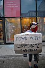 Photo: A woman holds a sign in front of a vandalized Scotia Bank minutes after the bank was attacked by the 'Black Bloc'
