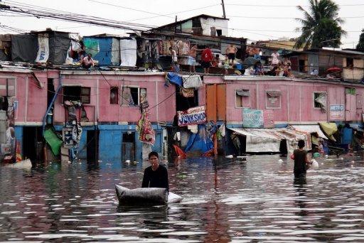 Photo: Un habitant traverse une rue de Manille submergée par les eaux, après les pluies torrentielles qui se sont abattues sur la capitale philippine. (© 2012 AFP)