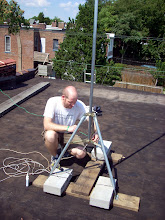 Photo: Wiring up a roof-top antenna mast.  Note that the mast tripod is not bolted to the roof, just anchored with cinderblocks.