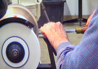 "Photo: Chuck sharpens his scrapers upside down, as do some other professionals.  Note that he's working below center on the grinder wheel to accomplish this.  He feels that it provides a better burr that way.  This is a screen shot off our new 55"" video monitor."