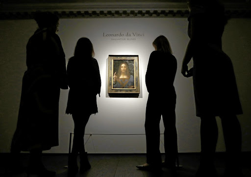 Christie's staff members pose next to Leonardo da Vinci's Salvator Mundi painting in London in October 2017. Picture: REUTERS