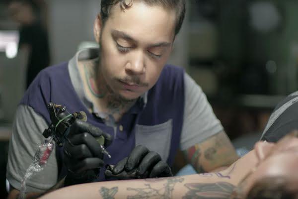 Resim: Jasmine bir müşteriye dövme yapıyor.