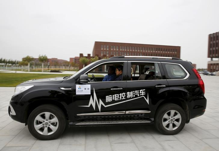 Researcher Zhang Zhao wearing a brain signal-reading equipment moves a car forward with his brain wave during a demonstration at Nankai University in Tianjin, China, November 17, 2015. REUTERS/Kim Kyung-Hoon