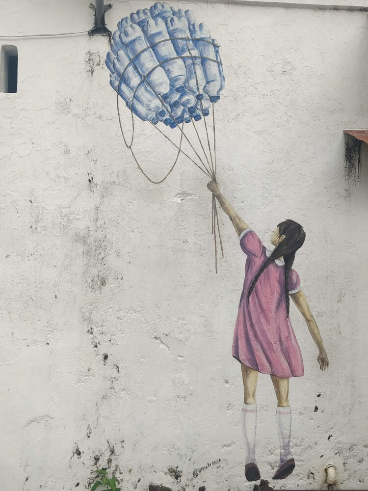 girl+reaching+up+balloon+street+graffiti+penang+town+malaysia