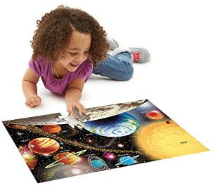 Little girl working with floor puzzle