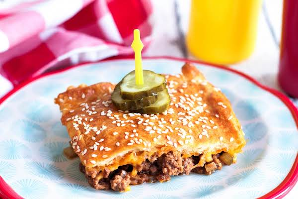 A Slice Of Cheeseburger Casserole On A Plate With Pickles.