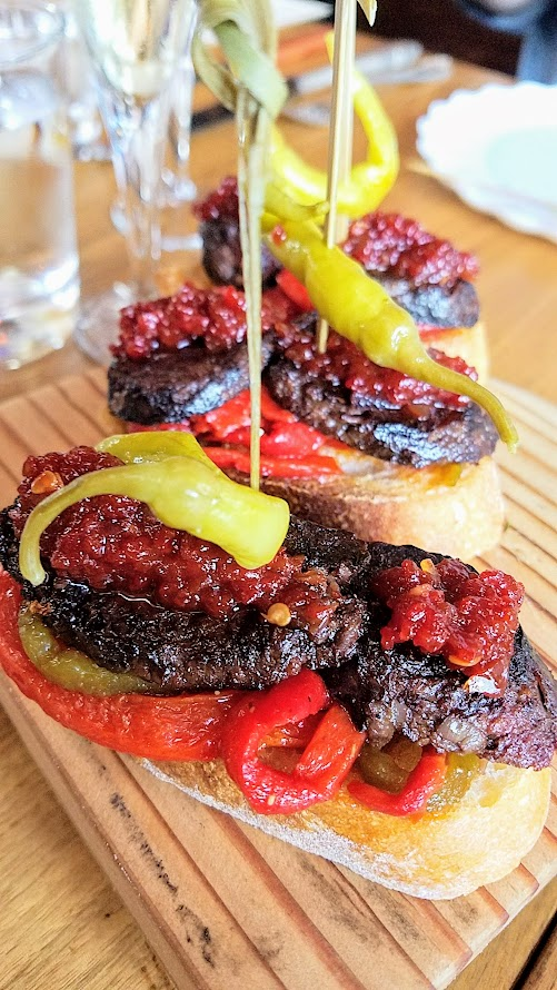 Pinxtos at Urdaneta: here you see Morcilla, grilled blood sausage, dad's marinated peppers, piquillo jam, piparra, toasted bread