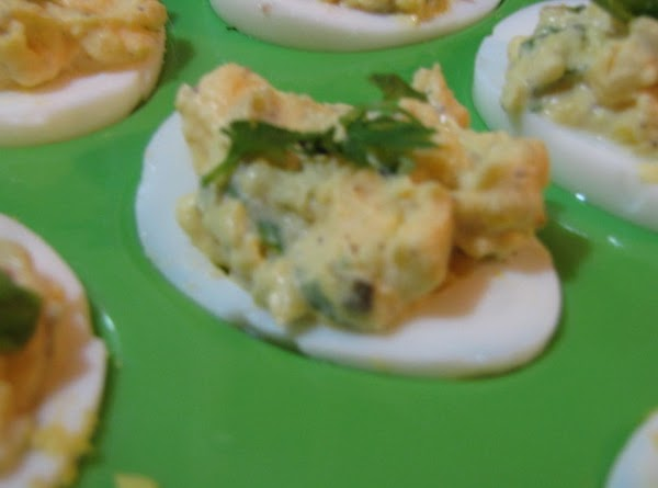 Place the yolk mixture in your egg white halves and garnish with a piece...