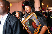 Vela Nyembe, slain deputy principal Hubert Nyembe's aunt, holds his picture as they carry him to his final resting place  on Saturday in KwaThema, Ekurhuleni. Photos:  KABELO MOKOENA