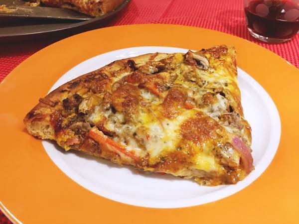 A Slice Of Pizza On An Orange/whiter Plate With Toppings And Melted Cheese.