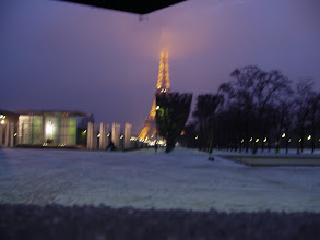 Photo: A change of scenery – and weather! We arrive in Paris to slushy snow, and there is a light covering at dusk on the Champs de Mars in front of the Eiffel Tower. You can see a bit of my umbrella at the top, keeping the falling precipitation off the camera.
