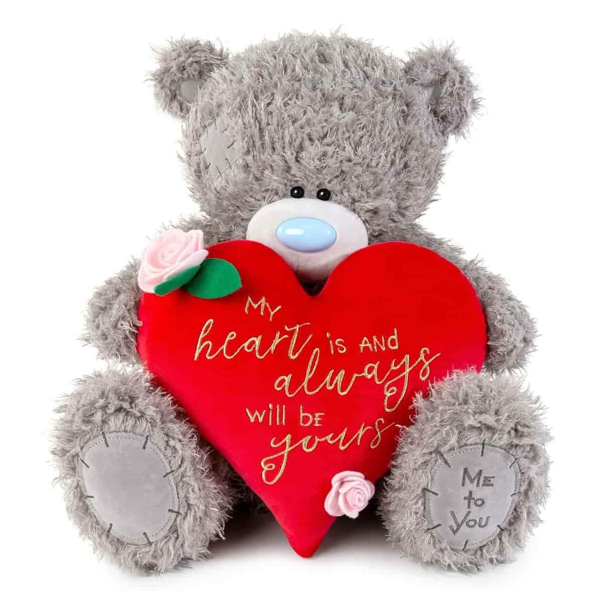 A grey soft toy; teddy bear holding a red coloured heart.