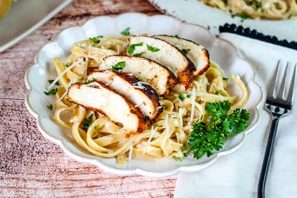 Sliced Blackened Chicken Breast With Fettuccine Alfredo.